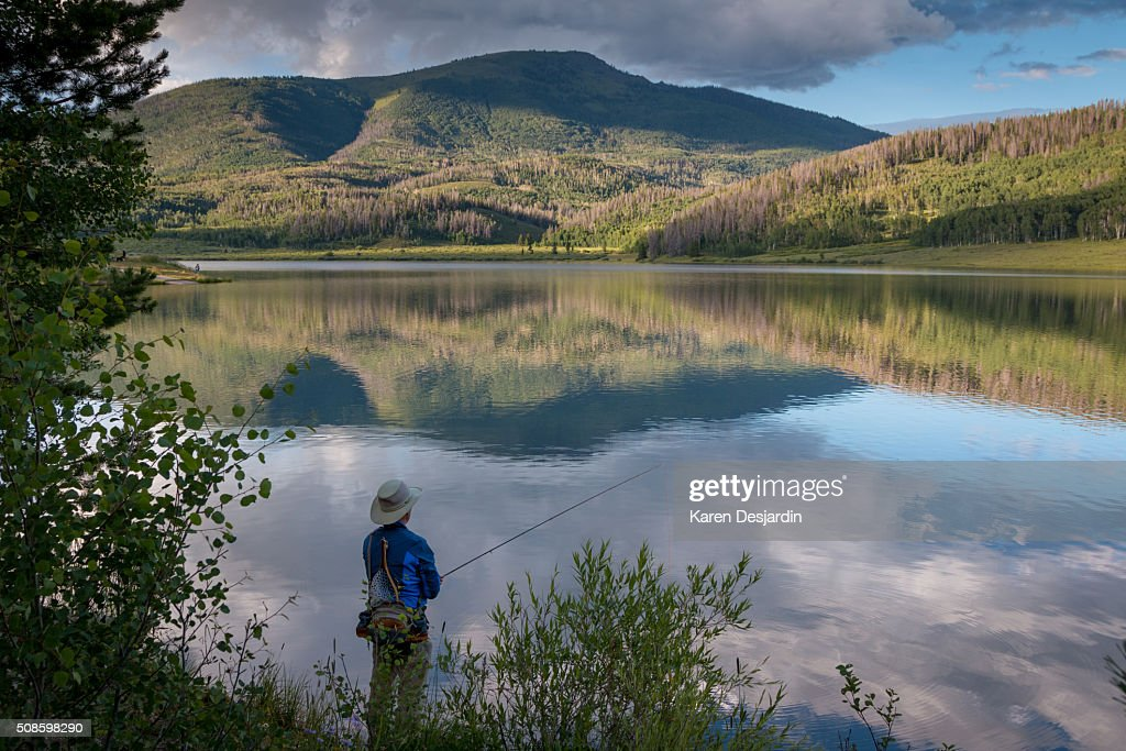 Fly fisherman at mountain lake with reflections, Colorado : Foto de stock