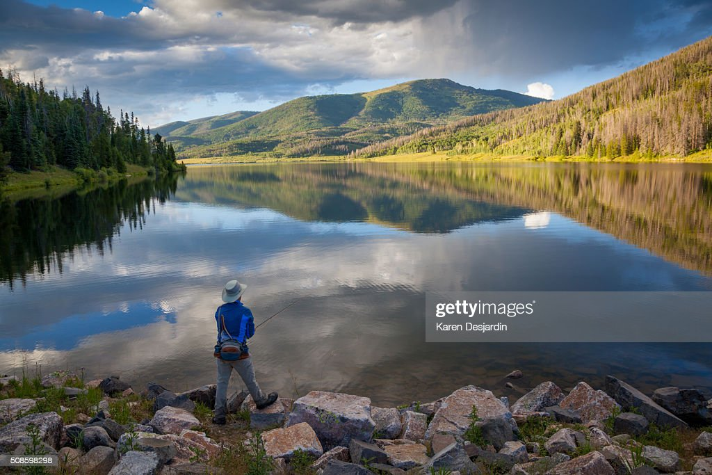fly fisherman at mountain lake with reflections, Colorado : Stock Photo