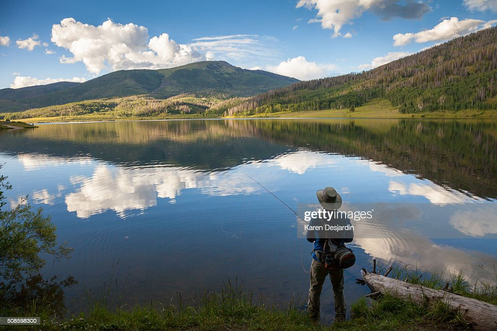 fly fisherman at mountain lake with reflections : Foto de stock