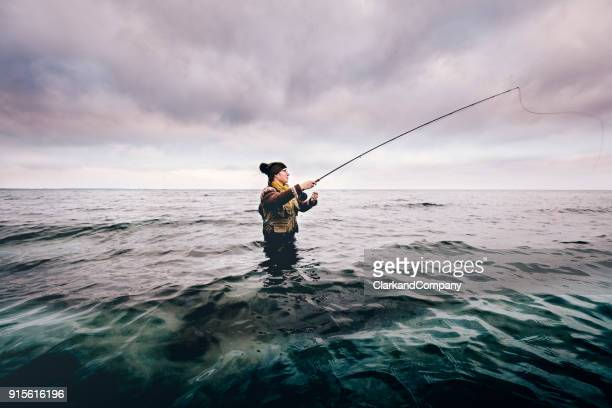 fly fisherman casting out her line - fishing stock pictures, royalty-free photos & images