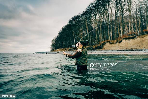 fly fisherman casting out her line - fly casting stock pictures, royalty-free photos & images