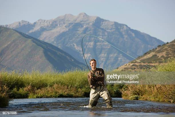 fly fisherman fishing in a mountain river - fly fishing stock photos and pictures