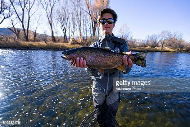 fly fisherman holding caught rainbow trout - big fish stock pictures, royalty-free photos & images