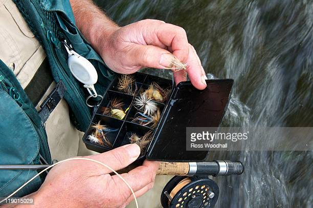fly fisherman holding fly box in river - fishing tackle stock pictures, royalty-free photos & images