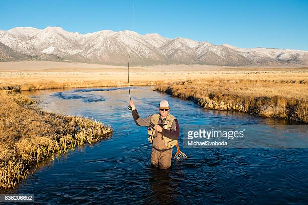 fly fisherman on the river casting - fly casting stock pictures, royalty-free photos & images