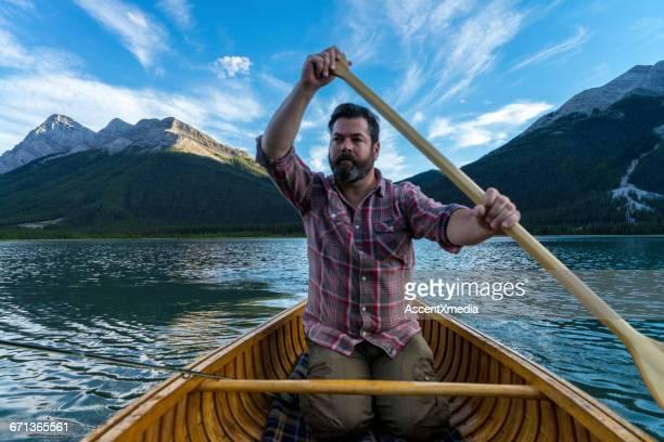 Fly fisherman paddles canoe, mountain lake