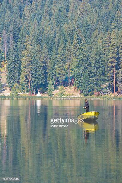 Fly Fisherman standing in boat on lake