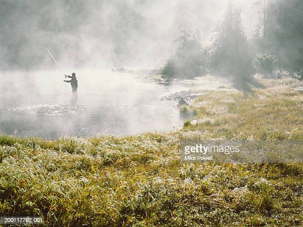 fly fisherman standing in lake covered with fog, casting, silhouette - whistler british columbia stock pictures, royalty-free photos & images