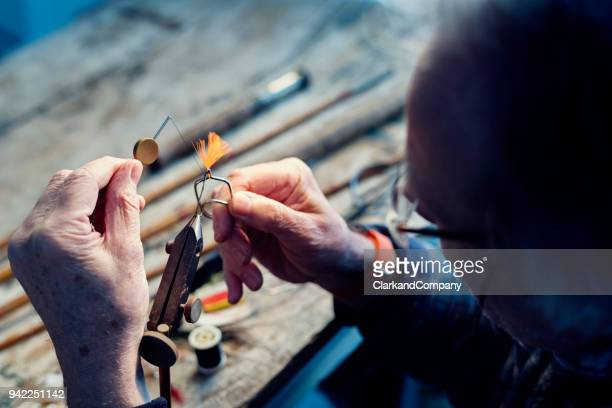 fly fisherman tying flies for ready for fishing - fishing hook stock pictures, royalty-free photos & images