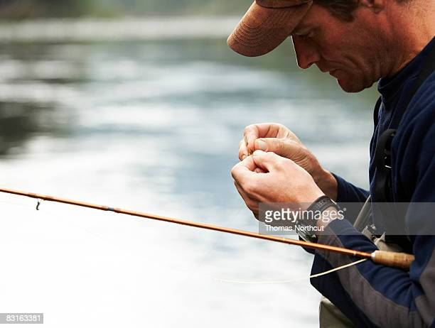 fly fisherman tying lures - fishing hook stock pictures, royalty-free photos & images
