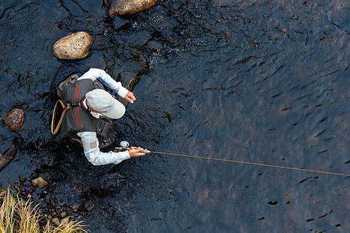 Fly fisherman using flyfishing rod 1024167146