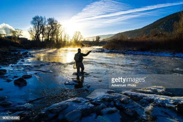 fly fisherman winter fishing - fly casting stock pictures, royalty-free photos & images