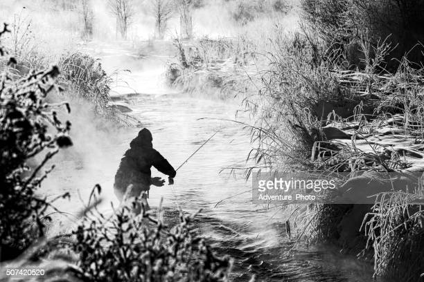 fly fishing in extreme cold winter conditions - fly casting stock pictures, royalty-free photos & images