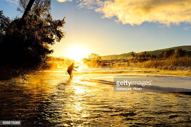 fly fishing in winter at sunrise - fly fishing stock photos and pictures
