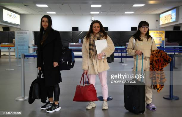 FLybe customers Jessica Cahna Abbey Fletcher and Robyn Kent who had a flight booked to with Flybe to Jersey pose for a photograph inside Exeter...