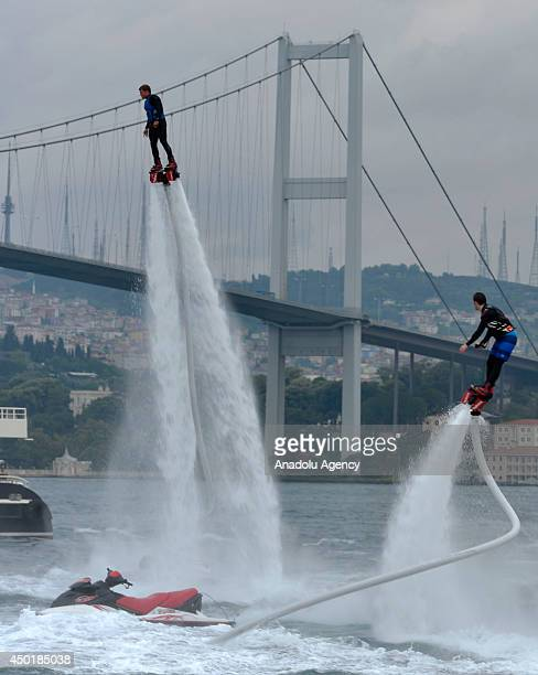 Flyboard riders practice by flipping in the air with a waterpropelled flyboard which connects to a personal water craft with a hose a head of the...