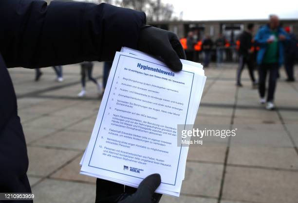 A flyer about Coronavirus is handed out prior to the Bundesliga match between Hertha BSC and SV Werder Bremen at Olympiastadion on March 07 2020 in...