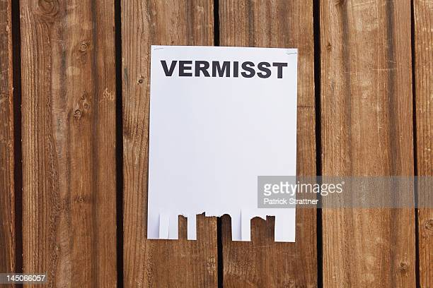 A flyer posted on a wooden fence with the German word for missing on it