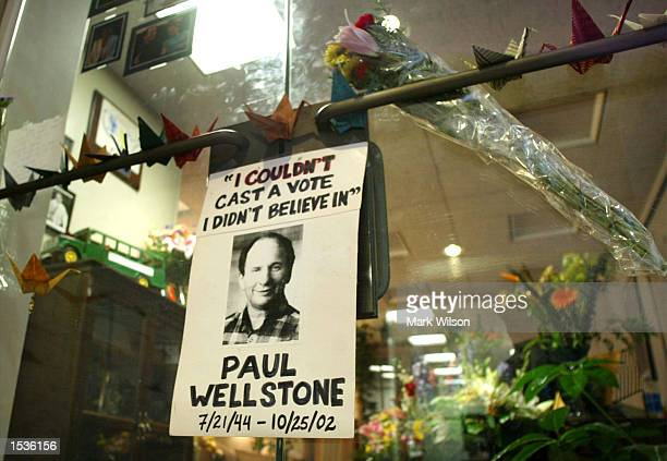 A flyer with a picture of US Senator Paul Wellstone reads I Never Cast a Vote I Didn't Believe In hangs with flowers on the front door of his office...