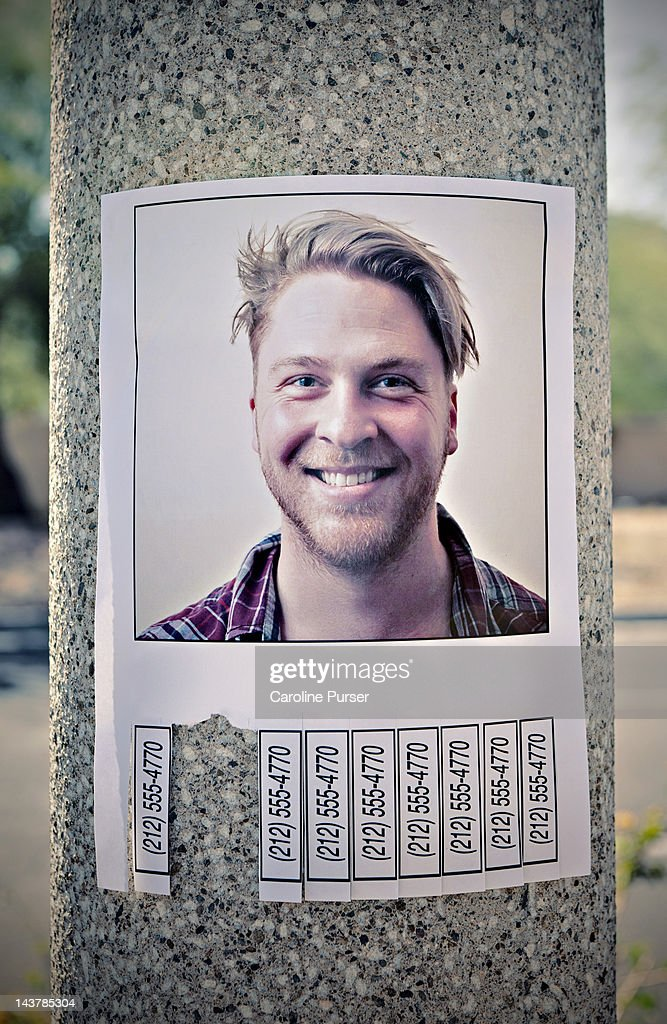 Flyer with phone numbers & man's picture on a post : Stock Photo