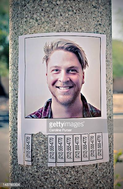 flyer with phone numbers & man's picture on a post - flyer leaflet stock photos and pictures