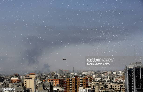 Flyers are dropped over Gaza City by the Israeli army urging residents to evacuate their homes on July 30 2014 Israeli bombardments early on July 30...