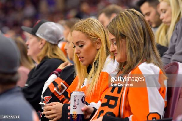 Flyers fans drink Corona and work their cell phones during the NHL game between the New York Rangers and the Philadelphia Flyers on March 22 2018 at...