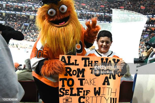 Flyers mascot Gritty poses with a sign holding fan during the regular season game between the Colorado Avalanche and the Philadelphia Flyers on...