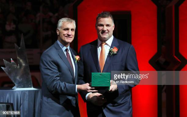 Flyers President Paul Holmgren presents a gift to Eric Lindros during his Jersey Retirement Night ceremony prior to a NHL game between the...