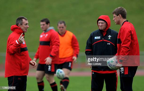 Flyhalf Rhys Priestland speaks with assistant coaches Neil Jenkins and Rob Howley during a Wales IRB Rugby World Cup 2011 media session at Newtown...