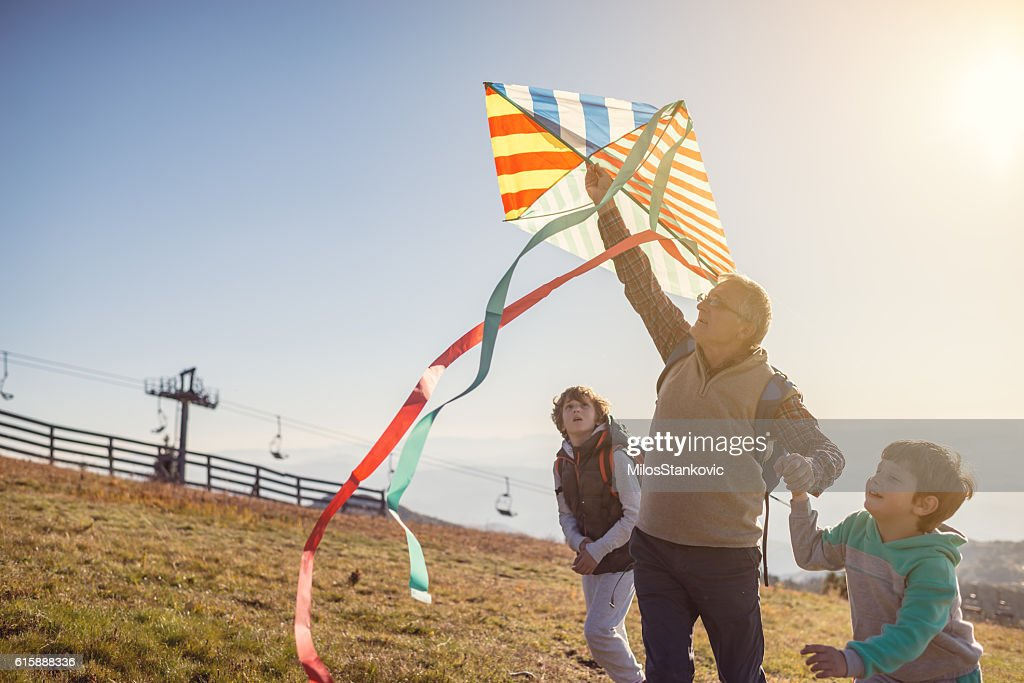 Flying a kite with Grandfather : Stock Photo