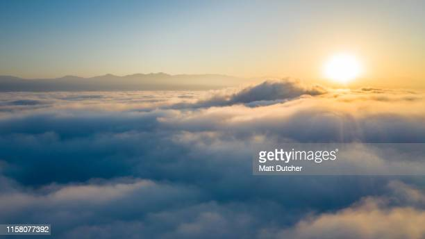 flying above the clouds - zonsopgang stockfoto's en -beelden
