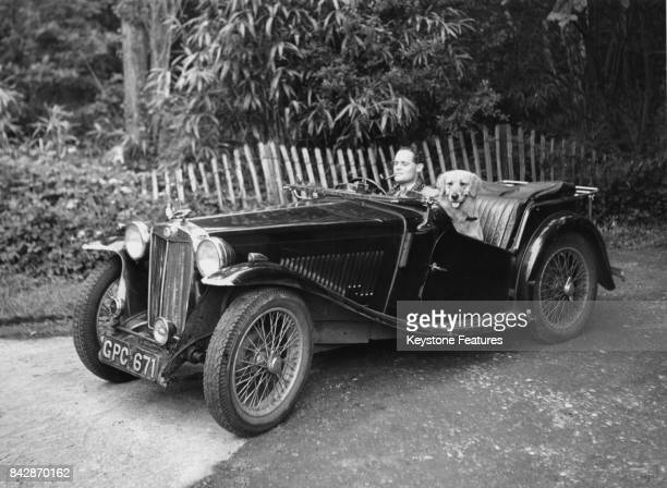 RAF flying ace Group Captain Douglas Bader out driving in an MG roadster with his dog Shaun after his release from a German prisonerofwar camp...