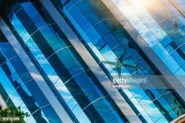 flying aeroplane refleced on glass building,detail shot