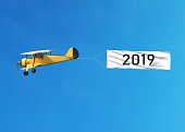 Flying airplane and Happy new year 2019 banner on blue sky