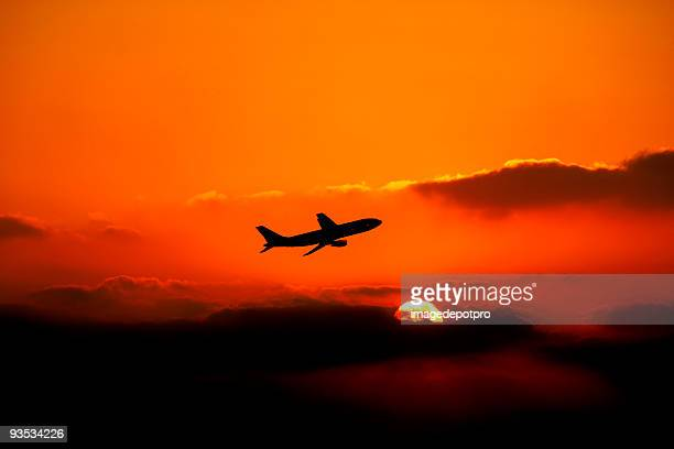 flying airplane over sunset