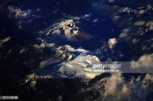 flying at sunset over a glacier in the italian alps - edoardogobattoni foto e immagini stock
