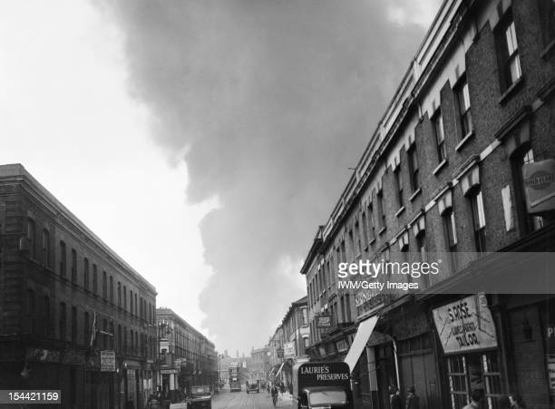 V1 Bomb Damage In London England UK A cloud of smoke rises in the distance after a V1 attack in the Norwood area of London Life appear to be...