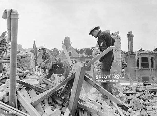 V1 Bomb Damage In London England UK Civil Defence wardens and a member of the American Ambulance Great Britain search amongst rubble and timbers for...