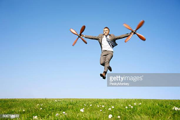 Flying Businessman Taking Off with Propellers in Meadow