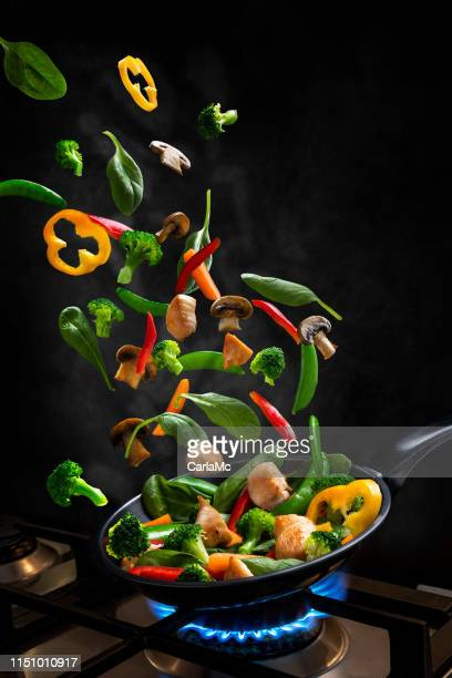 flying chicken and vegetable stir fry, into a frying pan - volare foto e immagini stock