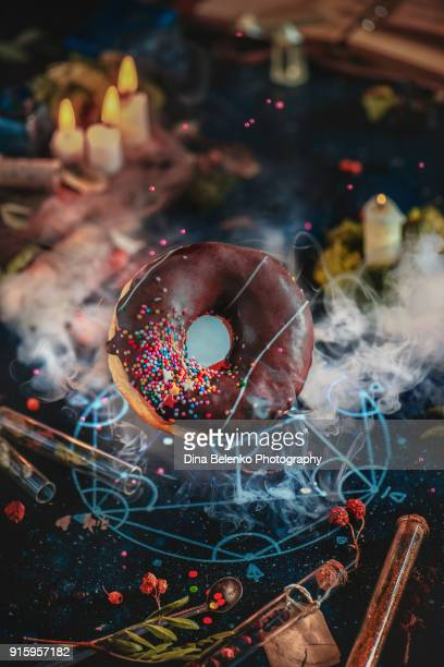 Flying chocolate glazed donut summoned with an alchemical pentagram. Magic recipe cooking. nceptual food photography.