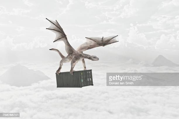 Flying dragon carrying cargo container in clouds