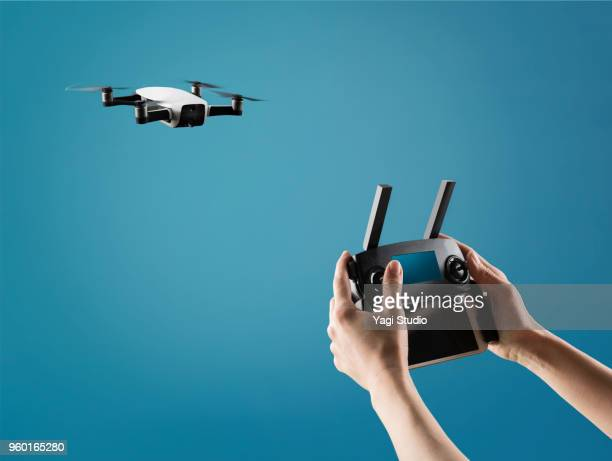 a flying drone with control device. - drone photos et images de collection