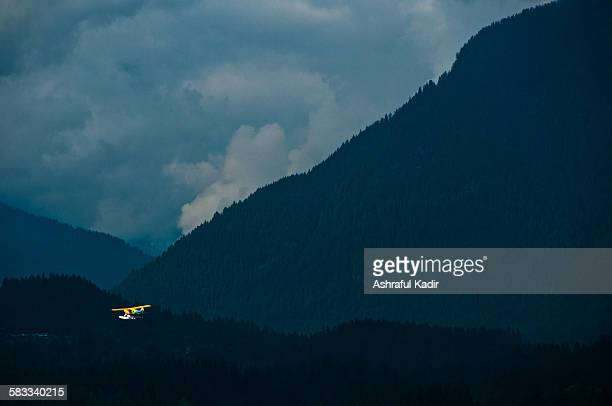 Flying floatplane and mountains, clouds
