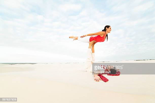 Flying Forward acro yoga couple in dunes