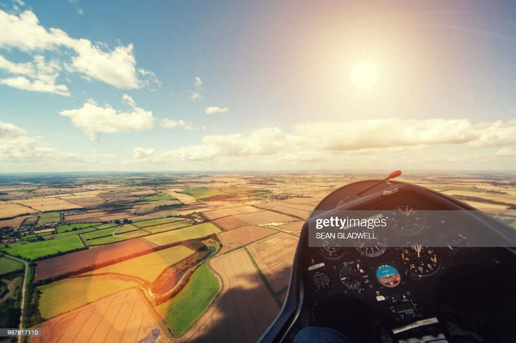 Flying glider aircraft over farmland with sun in sky : Stock Photo