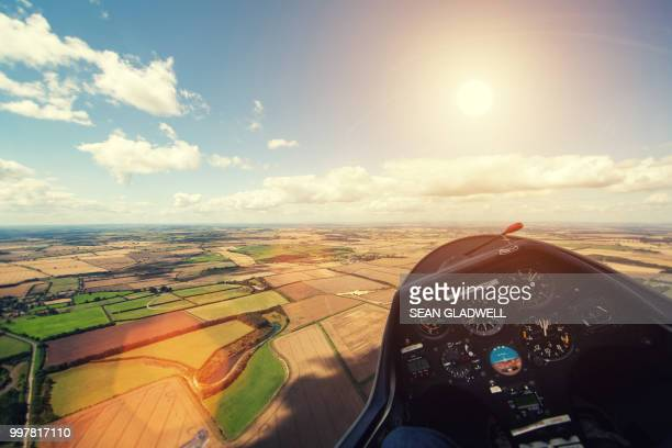 flying glider aircraft over farmland with sun in sky - glider - fotografias e filmes do acervo