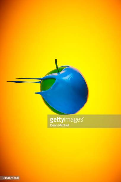 flying green apple with blue paint - dean foods stock photos and pictures