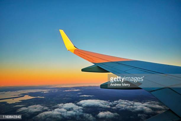 flying in airplane, airliner, aeroplane at high altitude with view of aircraft wing - tourism stock pictures, royalty-free photos & images